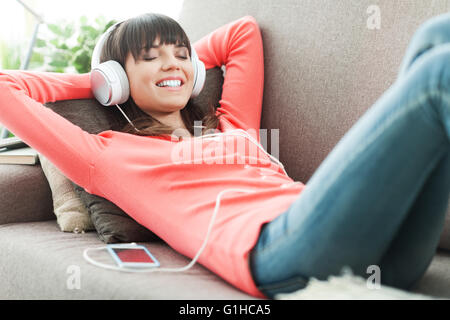 Young attractive woman relaxing on the couch at home, she is listening to music with headphones - Stock Photo