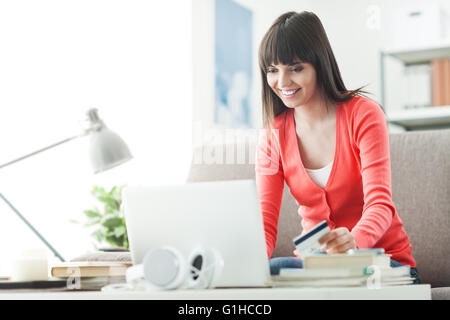 Young smiling woman at home using a laptop and shopping online with a credit card, commerce and communication concept - Stock Photo