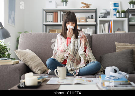 Sick woman with cold and flu, she is resting on the sofa at home and measuring body temperature with a thermometer - Stock Photo
