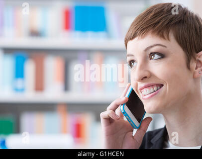 Smiling confident businesswoman on the phone, she is calling with a smart phone - Stock Photo