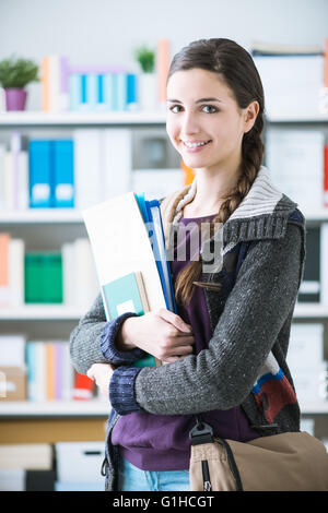 Confident smiling college student posing in the library, she is smiling at camera and holding notebooks - Stock Photo