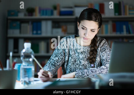 Young student girl doing her homework at home, she is writing and using a laptop - Stock Photo