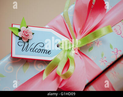 A gift wrapped box in light blue paper with pale pink roses and welcome card - Stock Photo