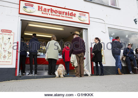 People queue outside the Harbourside ice cream shop in the Cornish seaside town of Mevagissey on a bright spring - Stock Photo