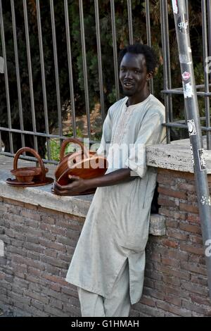 An African man selling hand made goods on the street in Rome - Stock Photo