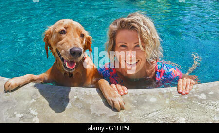 Funny portrait of smiling woman playing with dog and training golden retriever puppy in blue swimming pool. - Stock Photo