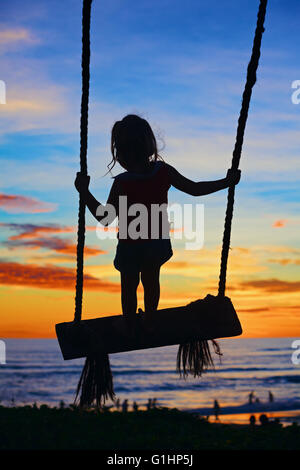 Black silhouette of happy baby girl flying high with fun on swing on ocean beach surf and blue orange sunset sky - Stock Photo