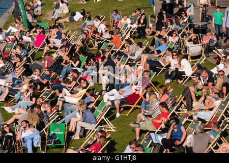 People sitting in afternoon beside River Spree at outdoor bar in Berlin Germany - Stock Photo