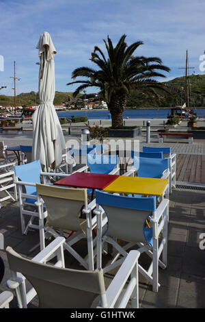 Empty multi-colored tables & seats from street cafes on Myrina's pedestrian access sidewalk at the port. Limnos - Stock Photo