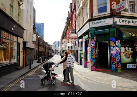 Asian couple with baby in pushchair crossing road in East London - Stock Photo