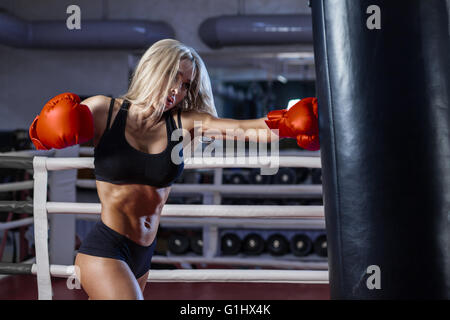 attractive young woman boxing at the gym - Stock Photo