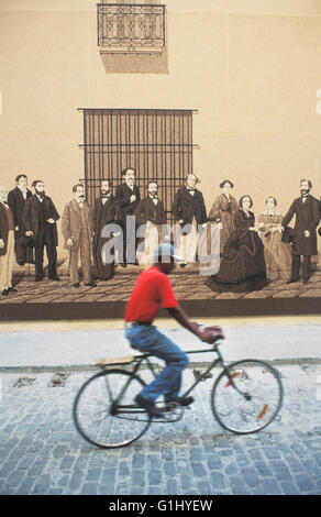 man in red shirt rides bicycle past mural in street in Old Havana on Caribbean island of Cuba - Stock Photo