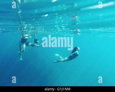 Three people swimming in the ocean - Stock Photo