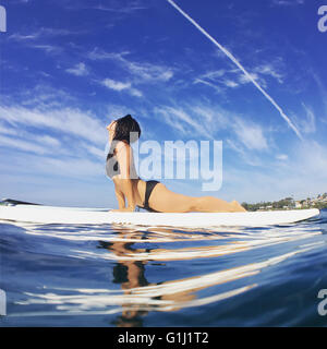 Woman doing yoga (cobra pose) on surfboard in ocean - Stock Photo
