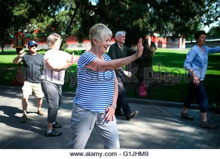 Some Foreign tourists practice Chinese tai chi under the guidance of the Chinese teacher at the temple of heaven - Stock Photo