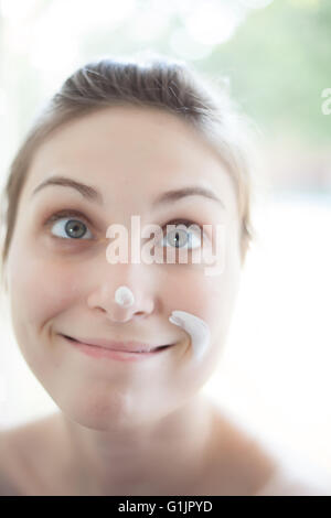 High key portrait of young women decorating her home making funny face - Stock Photo