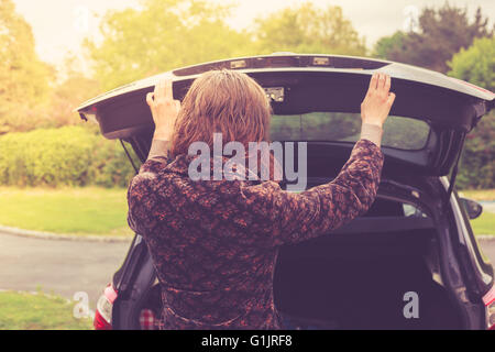 A young woman is opening the trunk of a car - Stock Photo