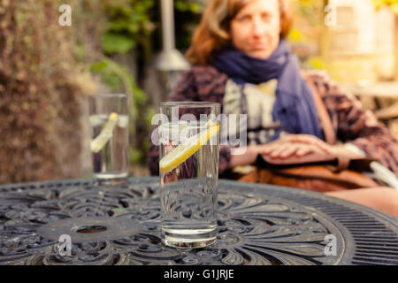 A young woman is sitting at a table and drinking in a garden - Stock Photo