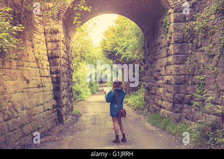A young woman is lost in a forest below a railway bridge and is studying a map - Stock Photo