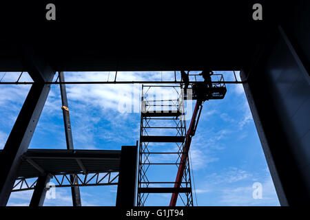 Workers are high up in cherry picker on building site. - Stock Photo