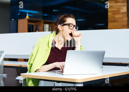 Pretty overworked young businesswoman in glasses yawning and using laptop on workplace - Stock Photo