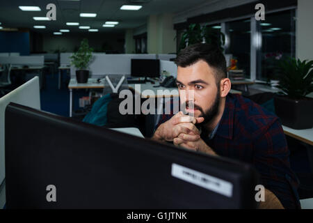Handsome bearded young businessman sitting on workplace and working late - Stock Photo