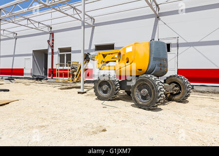 Cherry picker parked next to a newly painted metal frame building. - Stock Photo
