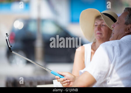 Middle-aged couple taking pictures with a phone - Stock Photo