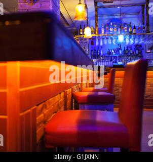 Seats in a brightly lit cocktail bar or nightclub - Stock Photo