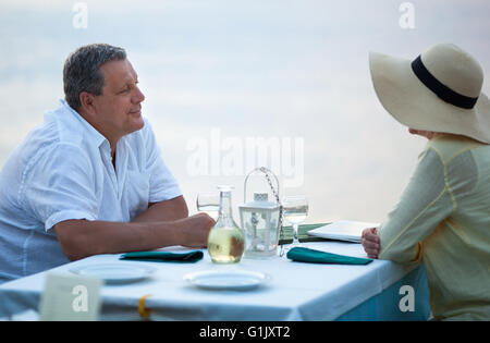 Middle-aged couple sitting waiting for a meal - Stock Photo