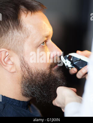 Man having his mustache trimmed at a barber - Stock Photo