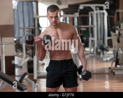 handsome young muscular man doing exercises in a fitness gym - Stock Photo