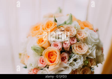 Bridal bouquet made of white, pink and orange roses with two wedding rings on top. Close-up - Stock Photo
