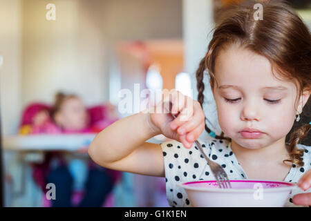 Little girl in the kitchen smiling, eating spaghetti - Stock Photo