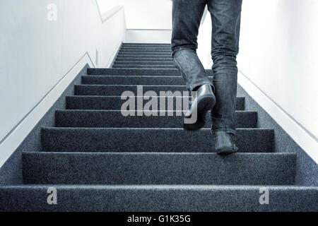 Man walking upstairs on staircase - Stock Photo