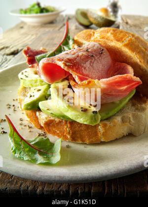 Prepared bacon and avocado sandwich in white bread on a plate - Stock Photo