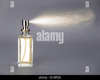 Bottle of perfume spraying - Stock Photo