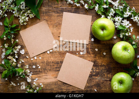 Beautiful spring/summer background: apple blossoms and fresh green apples on textured wooden backdrop. Empty vintage - Stock Photo