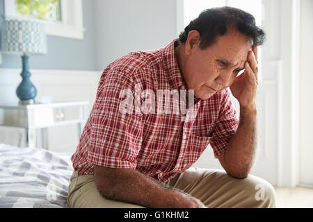 Senior Hispanic Man Sitting On Bed Suffering With Depression - Stock Photo