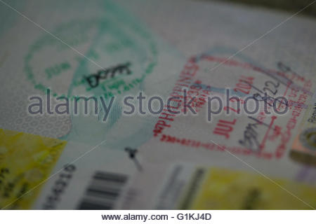 Immigration Red stamp in passport indicatiing arrival into the Philippines,Green stamp showing departure. - Stock Photo