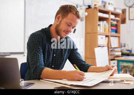 Young bearded male teacher at desk marking students' work - Stock Photo