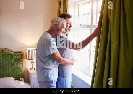 Male couple embrace looking out of their hotel room window - Stock Photo