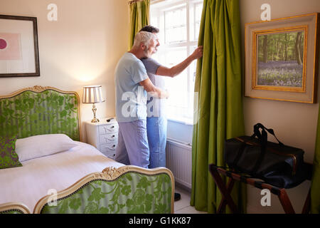 Male couple embrace looking out hotel room window, full length - Stock Photo