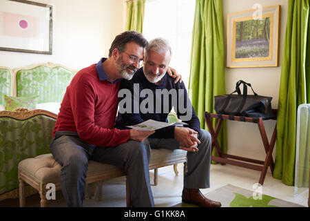 Male couple reading a guide brochure in their hotel room - Stock Photo