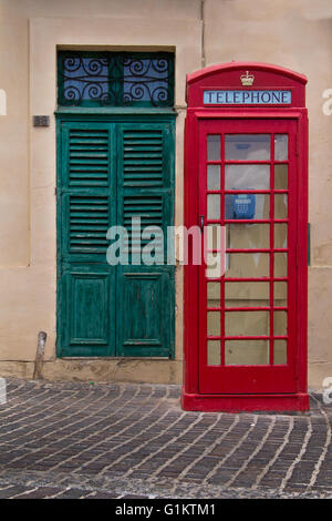 Traditional english style of a red telephone cabin. In the background green old gate. Street of fishing village - Stock Photo