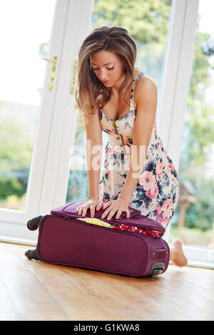 Girl struggling to close suitcase - Stock Photo