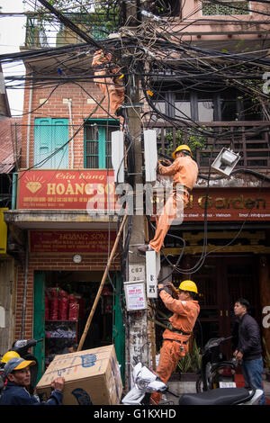 Men working on a telegraph pole in Hanoi's Old Quarter - Stock Photo
