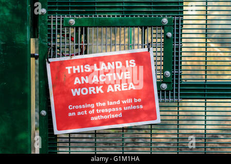 Security sign on a fence at a secure work site - Stock Photo