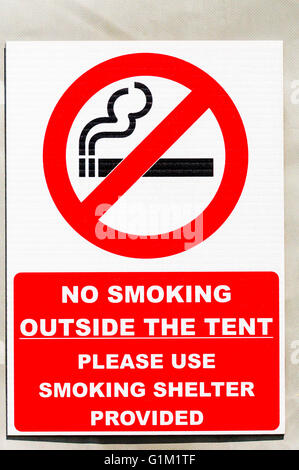 No smoking sign on a tent at a camp site, advising people to use the smoking shelter provided. - Stock Photo