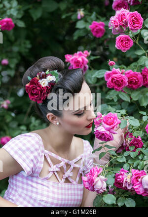 Beautiful retro woman holding and smelling roses - Stock Photo
